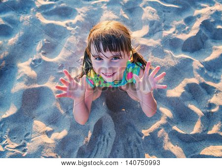 Little girl sitting on the sand at the beach looking up and showing his hand.