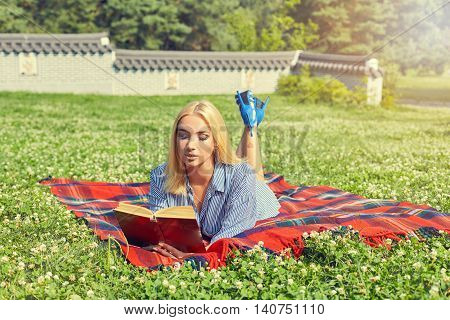 Beautiful young woman student reading book on grass, against background of summer green park. Beautiful girl on a red rug. Summer outdoor recreation. Natural happiness, fun and harmony.