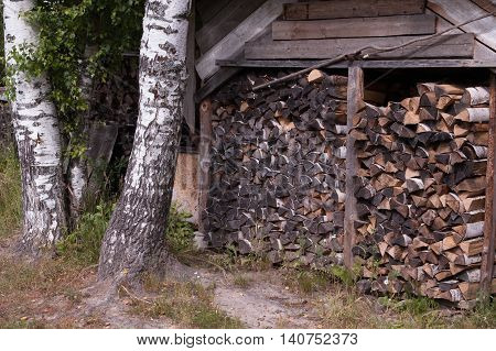 Shed for storage of birch firewood for heating the house by using the stove