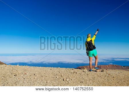 Woman successful hiking climbing people in mountains motivation and inspiration landscape on island and ocean. Hiker with arms up outstretched on mountain top looking at beautiful view on Tenerfie.