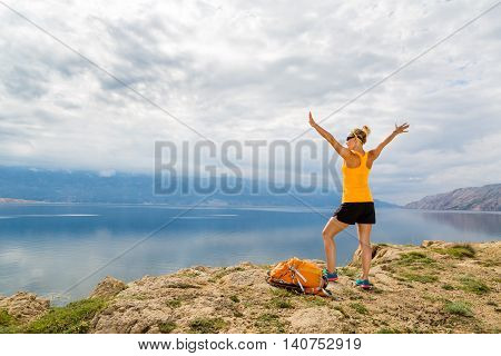 Woman hiking or climbing success arms outstretched looking at sea and mountains view. Accomplished climber with hands up outdoors. Beautiful inspirational landscape. Trekking and activity concept.