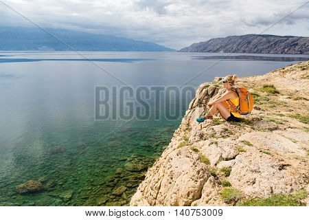 Woman hiker hiking with backpack looking at sea and mountains view. Recreation and healthy lifestyle outdoors in summer nature. Beautiful inspirational landscape. Trekking and activity concept.
