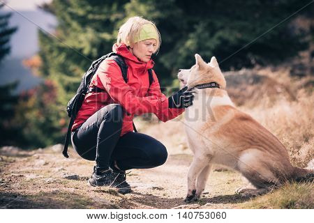 Woman playing with akita inu dog on hiking forest trail. Recreation and healthy lifestyle outdoors autumn woods in mountains inspirational nature. Fitness trekking and activity concept.