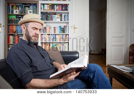 Man With Beard Reading A Book In His Living Room