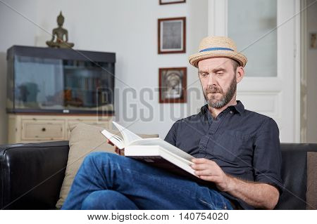 Man With Hat Reading A Book In His Leaving Room