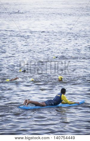 NEW YORK - JUL 24 2016: Lifeguards on surfboards patrol the route as athletes compete in the NYC Triathlon Race in New York. The swim portion is 1.5 kilometers in the Hudson River at Riverside Park.