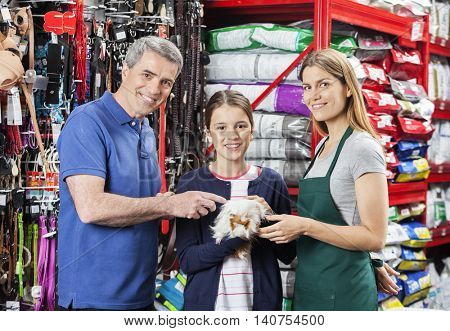 Girl Holding Guinea Pig With Father And Saleswoman In Store