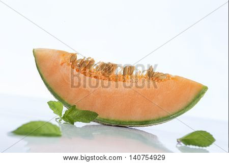 cantaloupe melon slices with basil leave on white