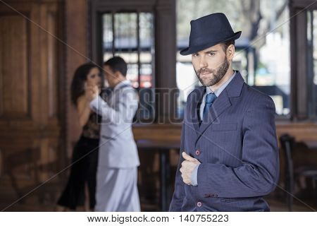 Confident Tango Dancer Standing While Partners Performing In Res