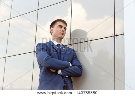 young successful man economist standing in modern office interior confident male dressed in luxury corporate clothes using digital tablet during work break
