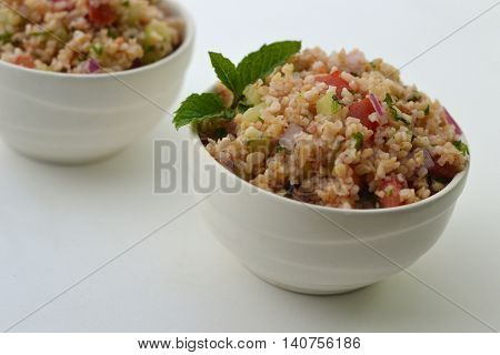 Tabouleh, sometimes spelled Tabbouleh, a traditional cracked wheat salad made with tomato, bulgur, cucumber, parsley, mint, lemon juice and olive oil.