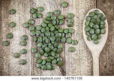 Spirulina,chlorella supplement pills in wooden spoon on table