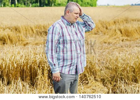 Worried farmer on destroyed cereal field .