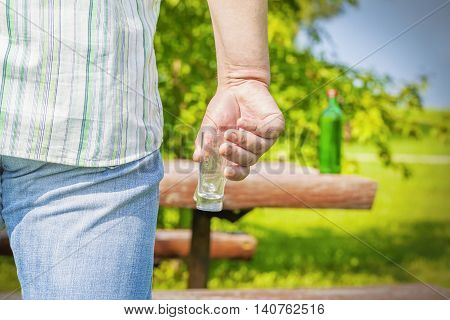 Man with glass near bottle of alcohol on table