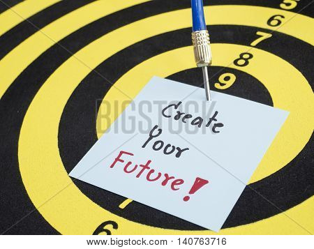 Handwriting Create your future on notepaper with dart arrow and dart board. (selective focus)
