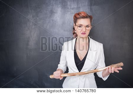Angry Teacher With Wooden Stick On Blackboard