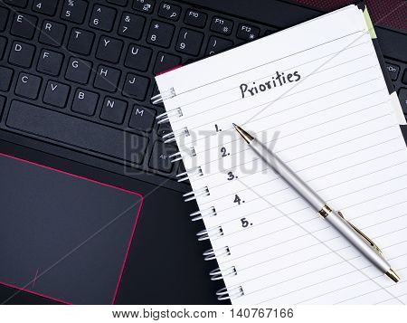 Handwriting Priorities on white notebook and pen with laptop keyboard background (top view)
