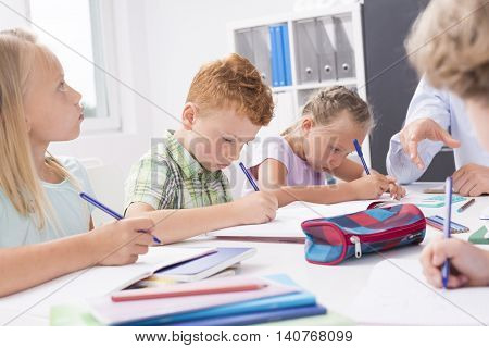 Shot of focused children sitting at the desk and solving the equations