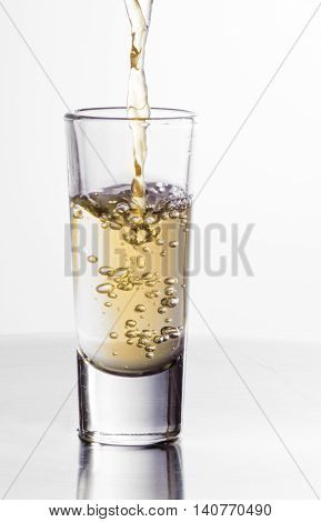 One tequila shot splash under the iron table in white background