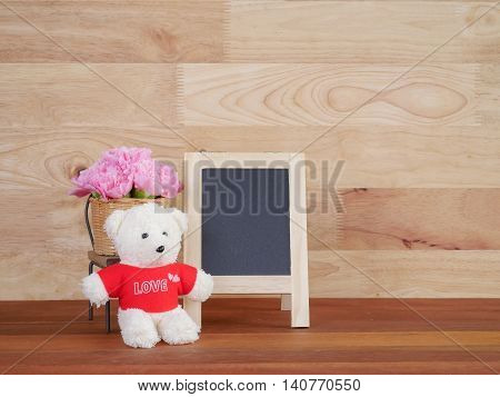 Blank blackboard bouquet pink Carnation flower and teddy bear on wood background (Love Concept)
