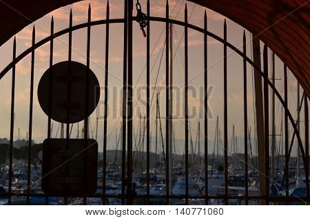 view on a port of yacht through a metal gate at the evening