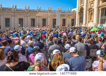 Rome, Italy - June 18, 2016: close up of people who listen to the Pope Francesco in St. Peter's Square for jubilee event. On background, the San Pietro Basilica.