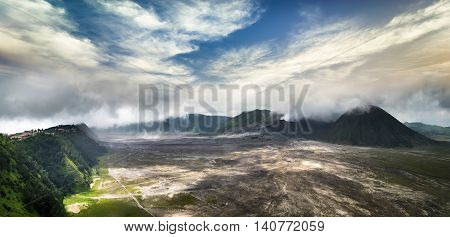 Amazing panorama view of mount Bromo with active volcano and village under cloudy sky. Java island landscape Indonesia