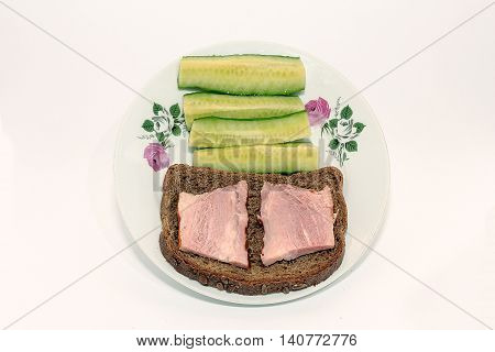 sandwich and cucumbers on a plate on white background