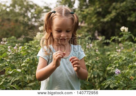 Little girl with a little plant standing in the garden on the windy summer day.