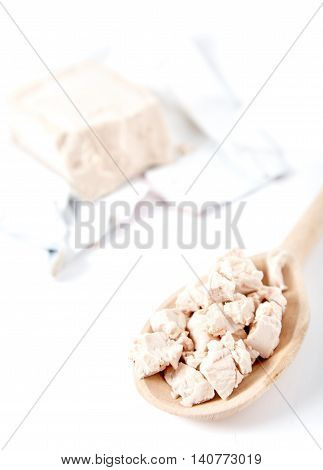 Fesh yeast on wooden spoon. Package of fresh yeast bar on back. Isolated on white image. Yeast is a main ingredient of fresh bread dough, pizza dough and many other dough's.