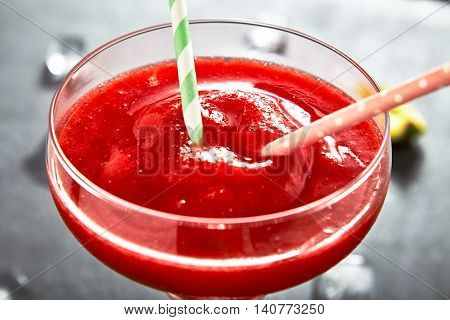 Close up of fresh frozen pureed strawberry margarita in margarita glass with two cocktail tubes in it, ice and limes near glass. Dark stone background.