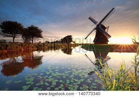 summer sunrise behind Dutch windmill in Holland