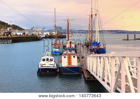 Brixham, Devon, Uk, Nov 02 2015: Small Boats Moored At A Jetty In The Harbour At Sunrise