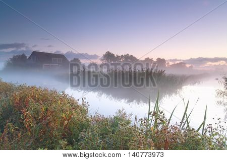 Dutch farmhouse by river in morning fog Netherlands