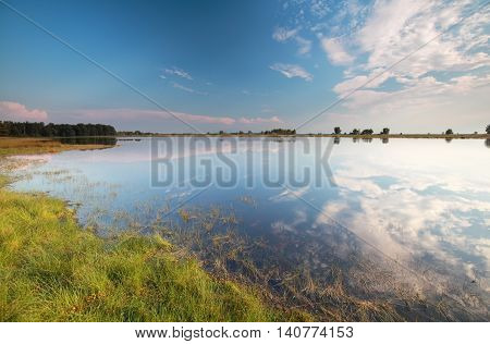 blue sky reflected in wild lake Drenthe Holland