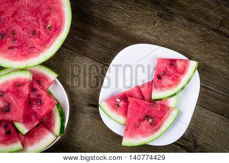 Triangle shaped watermelon slices placed in ceramic bowl on dark grungy background, top view