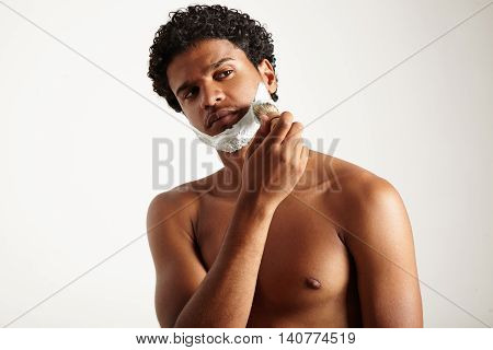 man watching aside and shaving topless on a white background