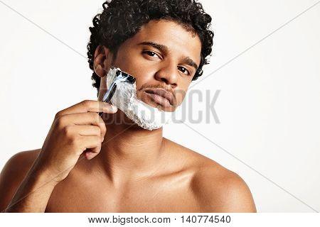 serious young shaving man looking at camera