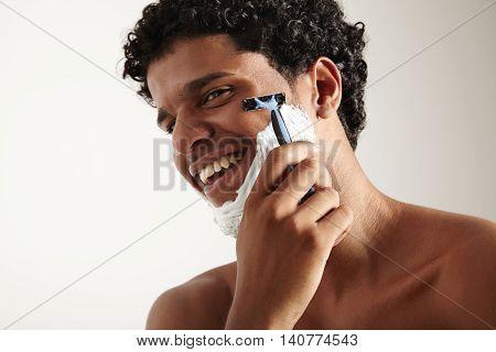 Smiling shaving man with razor on a white background