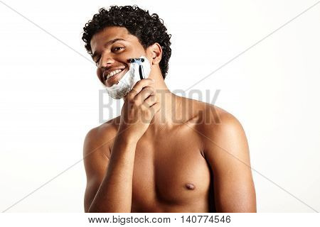 happy smiling man is shaving and looking at camera