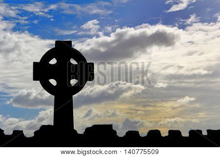 Celtic Cross Silhouetted Against A Dramatic Sky