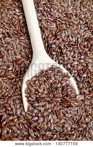 Wooden spoon with flaxseeds on background closeup