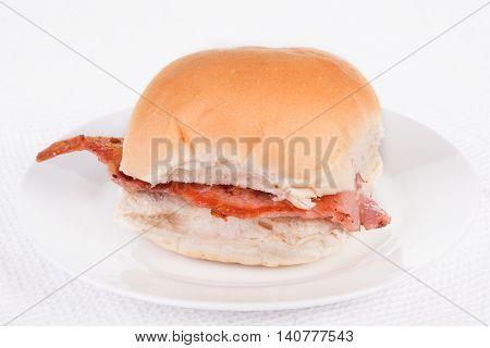 Bacon roll bap or bun on a white plate. Selective focus