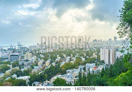 The sun rays among the hard grey clouds over Haifa Israel.