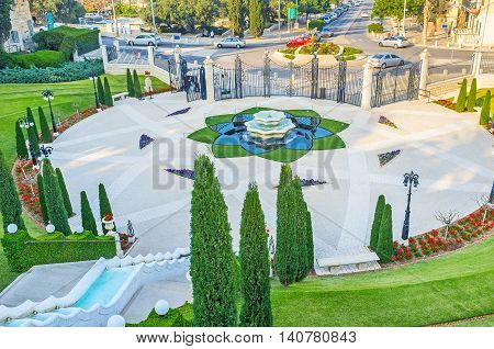 The scenic square decorated with the tiled pattern flower bed fountain in the middle surrounded by greenery and benches for visitors Haifa Israel.