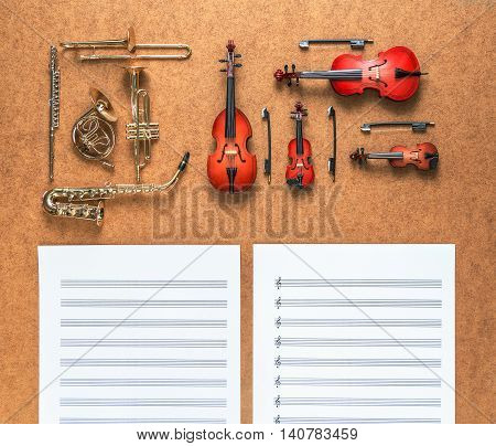 Set of five golden brass wind and four string musical orchestra instruments: saxophone, trumpet, french horn, trombone, violin, cello, contrabass, viola and sheet music lying between them.