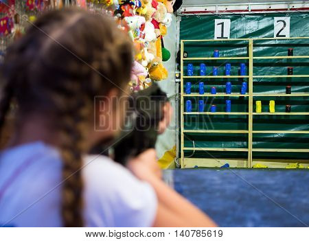 Alushta, Russia - June 02, 2016: The girl shoots from an pneumatic machine in the prize dash