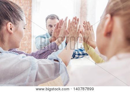 Coworkers doing high five sitting at the office table