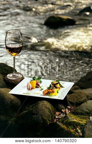 Picnic near water decorated fish meal with lemon glass of wine
