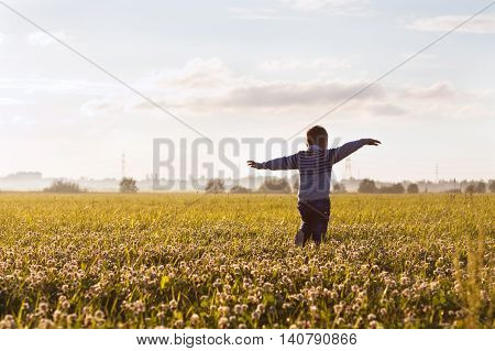 Little boy on the field in evening sunlight dreaming to fly like a plane.